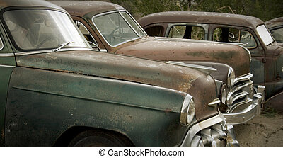 Old rusted cars in the rain at the junkyard looking sad. Good for themes of transportation, retirement, change, aging, retro, nostalgia, memories, family, friendship, humor.