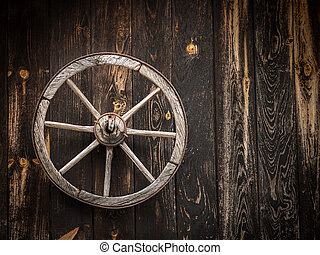 Old cartwheel hanging on a wooden barn