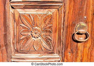 Old carved door with metal handle