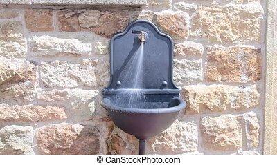 Old cast-iron basin on stony wall. The water runs down.