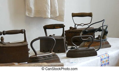 Old cast iron irons on display in the museum.