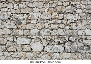 This is a texture of a wall made of single stone blocks. The stones are white colored and the seams dark which create a cobblestone like pattern over the whole picture. The rough surface / structure of the stone wall is very irregular and individual as the single stone blocks vary in size and shape...