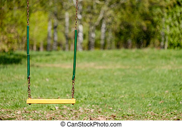 Old chain swing in the sun in the spring park