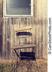 old chair on a rustic wooden wall