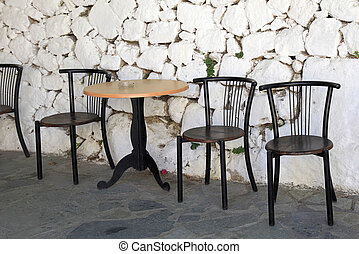 old chairs and white stone antique wall in greek village