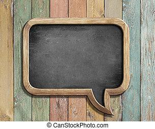 old chalkboard in shape of speech bubble on colorful wood 3d illustration