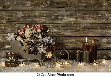 Old children toys and four burning advent candles on wooden vint