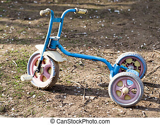 Old children's tricycle on nature