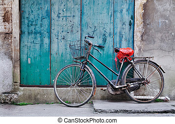 A Chinese-style bicycle, leaning against an old wooden door. Shot in Guilin, China.