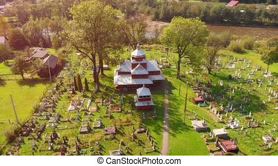 Drone view of an old, orthodox church and cemetery in Yaremche, a rural village on the Prut river in Ukraine.