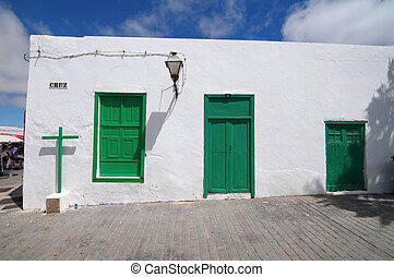 Old Church with green doors on a white wall