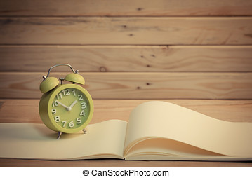 Old clock and book on a wooden table.