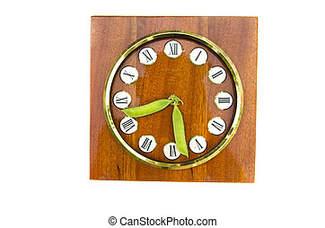 old clock dial with fresh pea pods arrows