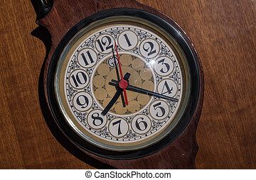 Old clock on a wooden table.