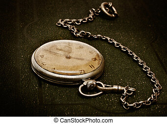Old clock with chain lying on rough green surface - Very old...