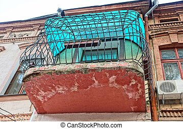 old closed balcony of iron bars on the wall with windows