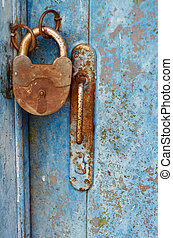 Old closed padlock rusty on wooden weathered door
