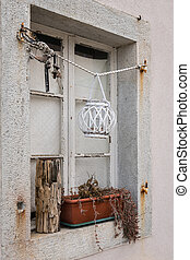 Old closed white window with decorations in front