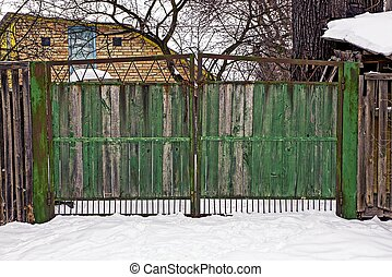 old closed wooden green gate in the street