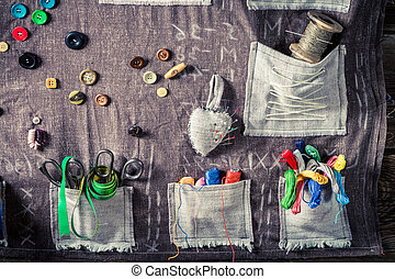 Old cloth with needles, scissors and threads in tailor workshop