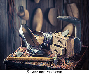 Old cobbler workshop with shoes, hammer and nails
