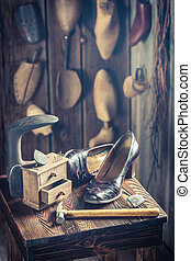 Old cobbler workshop with tools, shoes and leather