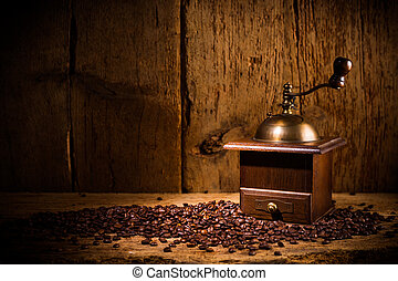 old coffee grinder with fresh roasted beans on rustic old vintage oak background