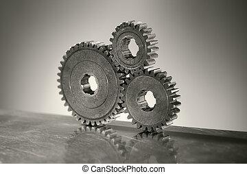 Monochrome still life of three old cog gear wheels. Short depth-of-field.