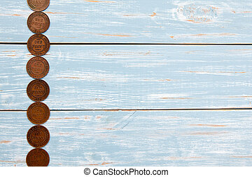 Old Coins on blue wooden background