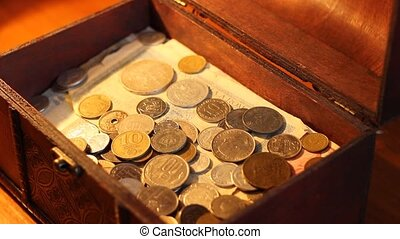 Hand pours coins into value wooden chest and plays greedy after with the money.