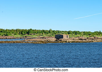 Old collapsing barn on the stone shore of the White Sea