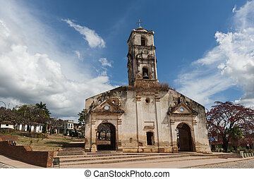 Old colonial church on a square in Trinidad, Cuba, with a sunny sky with clouds