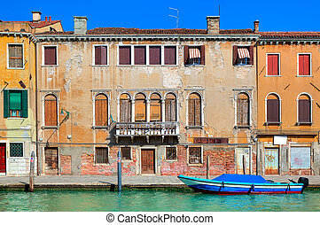 Old colorful house along narrow canal in Venice.