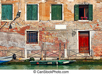 Old colorful house on narrow canal in Venice.