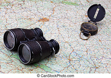 Old compass and binoculars on map