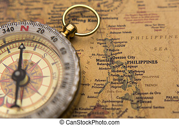 Old compass on vintage map selective focus on Philippines
