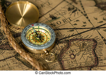 Old compass on vintage map with rope