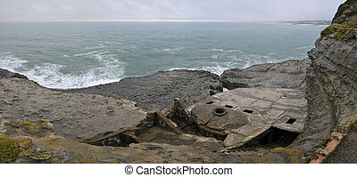 Old concrete blockhaus in a cliff with the sea during a sad day