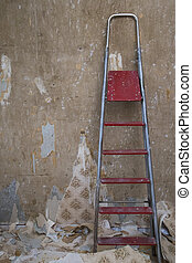 Old concrete wall with removed wallpaper and a ladder