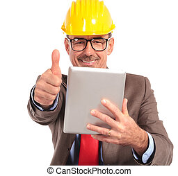 old construction engineer reading good news on his tablet pad