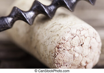 old corkscrew and wine cork on wooden surface macro closeup