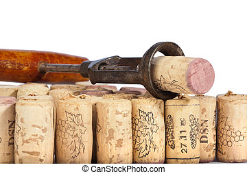 Old corkscrew with wood grip on many wine corks