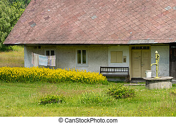 Old cottage with hand pump in the countryside.