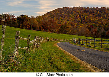 Old Country Road - Old country road winding by a fence in...