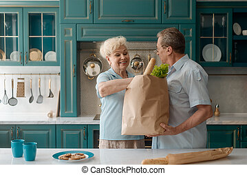 Old couple came home from grocery store and taking items out of a shopping bag