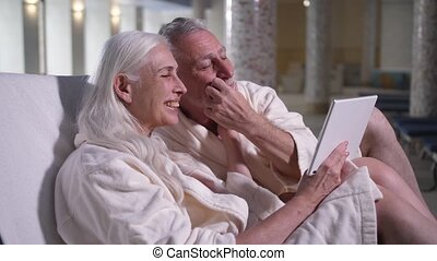 Old couple conversating online on tablet in hotel - Close-up...