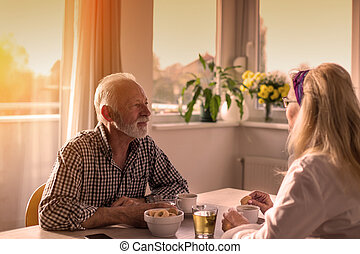 Old couple drinking coffee at table