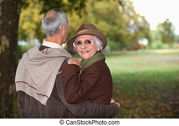 old couple in a park at autumn season