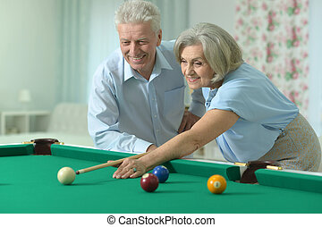 old couple playing billiard - Amusing old couple on vacation...
