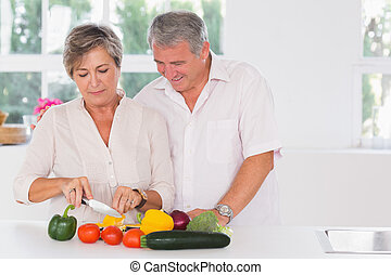 Old couple preparing vegetables in kitchen